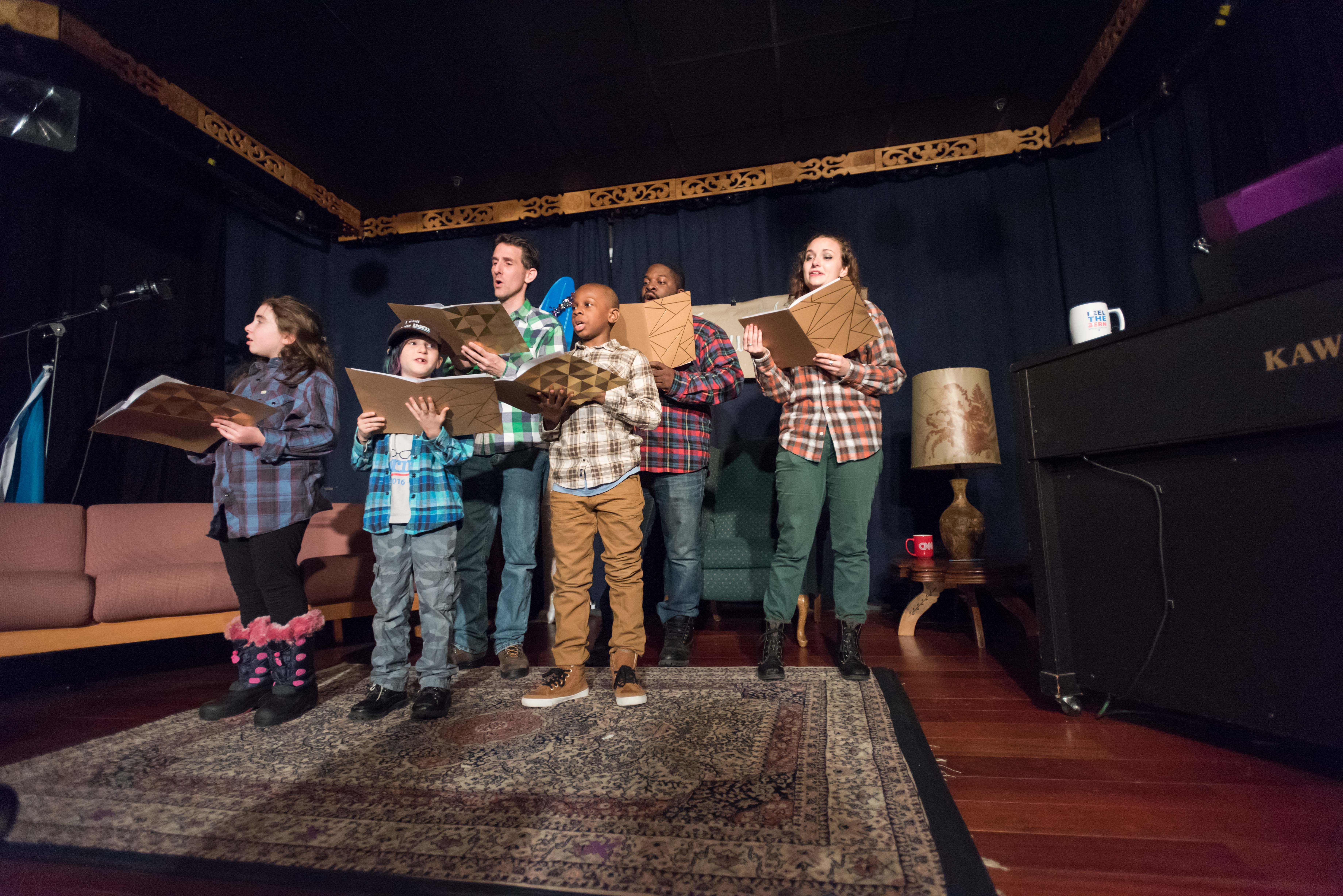 Back row, left to right: Jeff Epstein,Edson Sean,Kristin Freedman.<br> Front row: Ariel Eve, Brokaw, and Jaden Bullock singing from the hymnal of NotMeUs holiday songs.